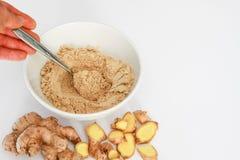 La poudre de gingembre dans la cuvette avec la main tenant la cuillère, racine de gingembre, gingembre rapièce en dehors de la cu Photo libre de droits