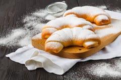 La poudre de sucre est vers?e sur un croissan fra?chement cuit au four images libres de droits