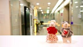 La poupée de couples de chèvre devant l'entrée de bureau Photos stock