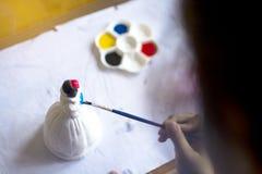 La poupée de plâtre de peinture de petit enfant avec la couleur d'eau bleue, concept d'art de pratique image stock