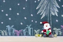 La poupée de Santa Claus se reposent sur le tableau noir avec un boîte-cadeau photographie stock