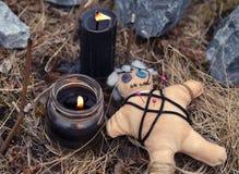 La poupée de vaudou avec brûler les bougies et l'encens noirs colle parmi des pierres photos stock
