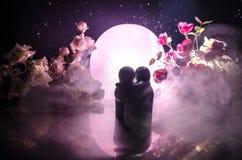 La poupée deux étreignant sur la table avec les fleurs et la décoration de lune a allumé le fond avec de la fumée Concept d'amour Photo stock