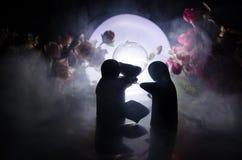 La poupée deux étreignant sur la table avec les fleurs et la décoration de lune a allumé le fond avec de la fumée Concept d'amour Photo libre de droits