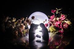 La poupée deux étreignant sur la table avec les fleurs et la décoration de lune a allumé le fond avec de la fumée Concept d'amour Photos libres de droits