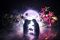 La poupée deux étreignant sur la table avec les fleurs et la décoration de lune a allumé le fond avec de la fumée Concept d'amour Photographie stock libre de droits