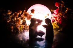 La poupée deux étreignant sur la table avec les fleurs et la décoration de lune a allumé le fond avec de la fumée Concept d'amour Image stock