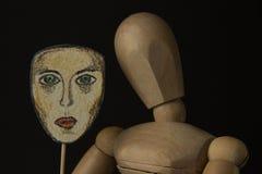 La poupée en bois sur des charnières tient un masque dans des mains et couvre son visage Photos stock