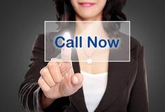 La poussée de femme d'affaires à appeler maintenant se boutonnent sur l'écran virtuel Photo stock