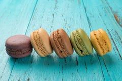La pousse de studio des macarons colorés alignent sur le fond bleu photographie stock