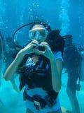La pousse sous-marine d'une plongée de femme et l'apparence aiment le signal Photographie stock libre de droits