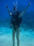 La pousse sous-marine d'une plongée de femme, met ses mains et showin Images stock