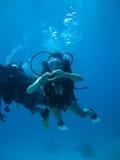 La pousse sous-marine d'une plongée de jeune femme et l'apparence aiment le signal Photographie stock