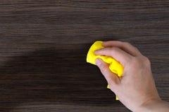 La poussière de main les meubles en bois images stock