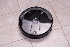 la poussière de nettoyage robotique d'aspirateur sur des planchers de tuiles Ménage futé moderne de technologie de nettoyage Fin  photographie stock
