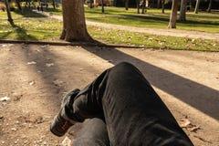 La POV delle gambe di un uomo ha attraversato la seduta su un banco in un parco all'aperto fotografia stock libera da diritti