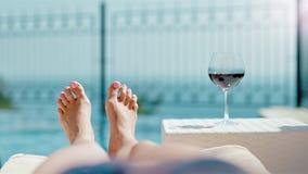 La POV ha sparato alla donna che si rilassa avendo sunbath che si trova sullo sdraio che gioca i piedi nudi con bocal di vino ros video d archivio