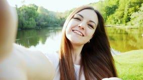 La POV ha sparato della giovane donna attraente prende il selfie sul telefono o la macchina fotografica, lago nella foresta su fo archivi video