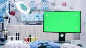 La POV a tiré du chimiste dans la combinaison blanche dactylographiant sur le keyborad d'ordinateur avec la maquette verte d'écra banque de vidéos