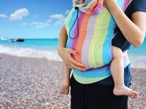 La práctica de Babywearing con el bebé que llevaba de la madre en la suavidad de SSC estructuró el portador en la playa fotografía de archivo