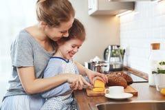 La préparation de la mère de petit déjeuner de famille et de la fille d'enfant a coupé b photos stock