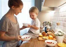 La préparation de la mère de petit déjeuner de famille et le fils de bébé font cuire le porrid photo stock