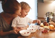 La préparation de la mère de petit déjeuner de famille et le fils de bébé font cuire le porrid photographie stock