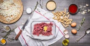 La préparation des boules de viande hachée crues avec la chapelure d'oeufs eggs la sauce tomate de pâte, oignons coupés en tranch Image libre de droits