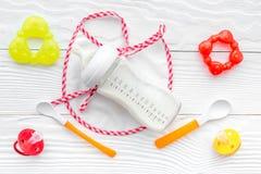 La préparation du bébé de mélange alimentant avec la formule infantile a saupoudré le lait dans la bouteille avec le bavoir sur l photo libre de droits