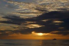 La première lumière derrière la mer, naviguant cependant le ciel Photos stock
