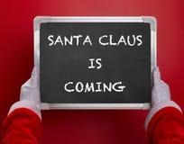 La première vue d'angle de personne de Santa Claus jugeant un panneau de craie noir écrit avec SANTA CLAUS VIENT sur le rouge Photo libre de droits