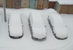 La première vue de la neige a couvert des véhicules Image libre de droits