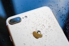 La prenda impermeable más de IPhone 7 con lluvia cae en backgroud de cristal posterior Foto de archivo