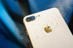 La prenda impermeable más de IPhone 7 con lluvia cae en backgroud de cristal posterior Imagen de archivo