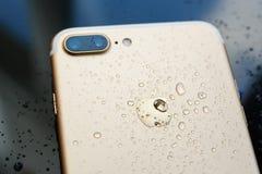 La prenda impermeable más de IPhone 7 con lluvia cae en backgroud de cristal posterior Imagen de archivo libre de regalías