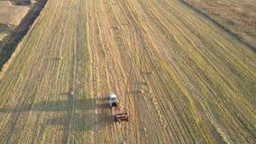 La prensa cuadrada de la visión superior recoge la paja en campo cosechado almacen de metraje de vídeo