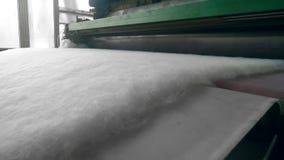 La prensa de batir funciona con el material del poliéster en una fábrica metrajes