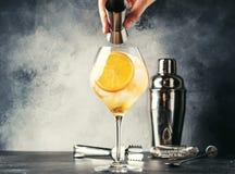 La preparación de Aperol spritz el cóctel, camarero vierte amargo del aparejo, bebida fría con poco alcohol italiana del verano,  foto de archivo libre de regalías