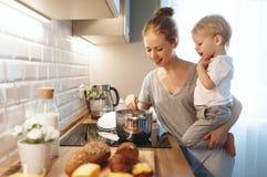 La preparación de la madre del desayuno de la familia y el hijo del bebé cocinan el porrid fotos de archivo libres de regalías