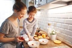 La preparación de la madre del desayuno de la familia y la hija del niño cocinan fotos de archivo