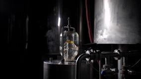 La preparación del agua en la fábrica de la cerveza, agua es de ebullición y de filtración en el frasco de cristal en la cuba del metrajes