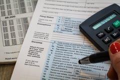 La preparación del impuesto forma la pluma de tenencia Fotos de archivo libres de regalías