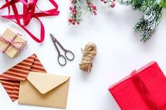 La preparación del partido del Año Nuevo con el embalaje de regalos en cajas y los sobres en el fondo blanco rematan el veiw Fotografía de archivo libre de regalías