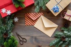 La preparación del partido del Año Nuevo con el embalaje de regalos en cajas y los sobres en fondo de madera rematan el veiw Fotografía de archivo libre de regalías