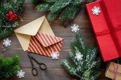 La preparación del partido del Año Nuevo con el embalaje de regalos en cajas y los sobres en fondo de madera rematan el veiw Foto de archivo libre de regalías