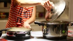 La preparación en la cocina, con un pote de ebullición la presentadora quita la tapa almacen de metraje de vídeo