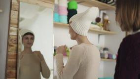 La preparación sonriente de la mujer hizo punto el sombrero y la mirada en espejo en sitio de la demostración almacen de metraje de vídeo