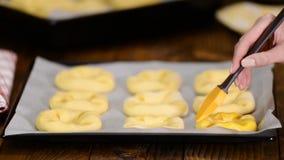 La preparazione dell'panini aperti casalinghi Vatrushka, pasticceria fresca, unge i panini con un uovo stock footage