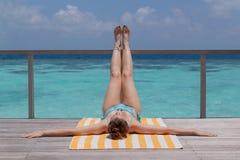 La presa della giovane donna si abbronza su un terrazzo Chiara acqua blu come fondo immagine stock