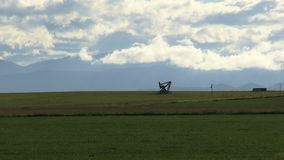La presa distante della pompa estrae l'olio fra il campo fresco contro le nuvole video d archivio